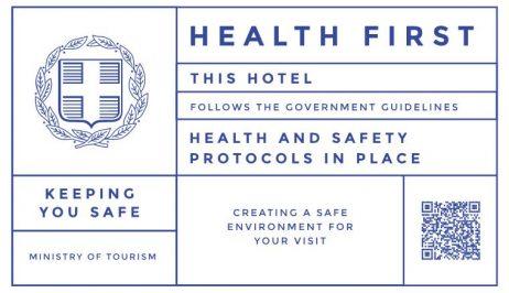 """Σήμα """"Health First"""" που δείχνει πως το Ruby Rooms ακολουθεί όλα τα πρωτόκολλα υγείας & ασφάλειας."""